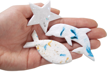 plantable memorials star, fish and dophin shapes shown in hand for size scale