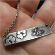 silver bar pendant engraved with 2 paw prints and name in 3D